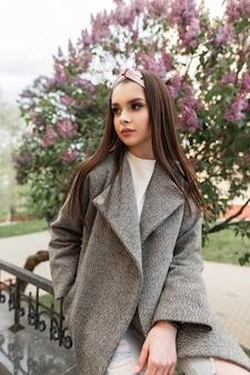ファッショナブルな灰色の春のコートのヴィンテージバンダナのファッションモデルの豪華な若い女性は、街の通りに紫色の花と花木の近くで休む。トレンディな若者の服を着たエレガントでスタイリッシュな女の子