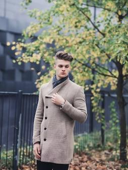 秋の公園でポーズのコートのファッションモデル男