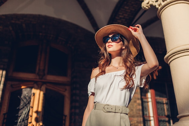 Манекенщица. внешний портрет туристской женщины наслаждаясь осмотром достопримечательностей во львове. девушка смотрит на древнюю архитектуру
