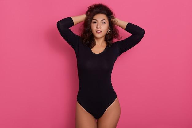 Модель позирует позирует на розовом фоне в черном платье