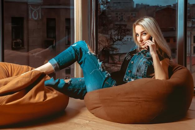 손에 휴대 전화와 함께 소파에 포즈와 찾고 패션 모델. 휴식, 다과 및 여가의 개념