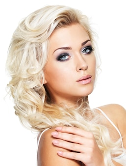 Fashion model posing . portrait of a beautiful blond woman with saturated makeup. girl posing on white wall