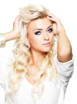 패션 모델 포즈. 포화 화장과 아름 다운 금발 여자의 초상화. 흰 벽에 포즈를 취하는 여자