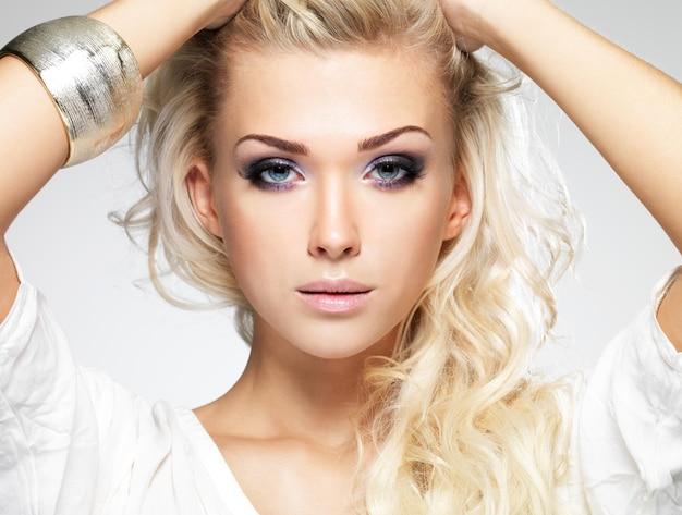 ファッションモデルのポーズ。飽和メイクで美しい金髪の女性の肖像画。白い壁にポーズをとる少女