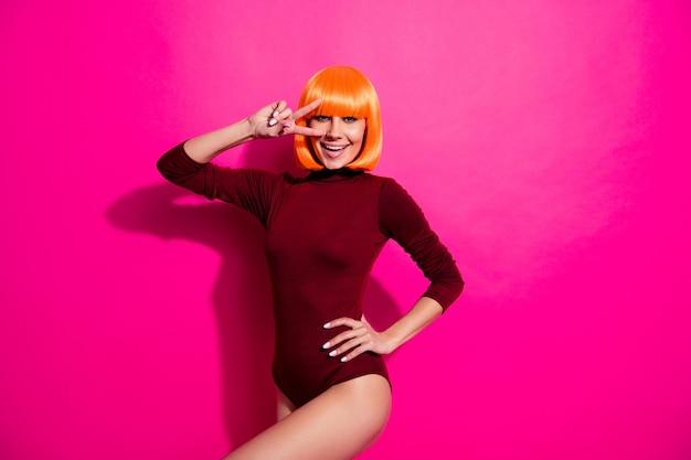 オレンジ色のかつらでポーズをとるファッションモデル