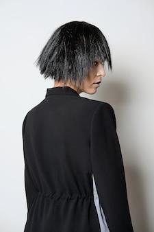 Fashion model in short black wig posing in profile