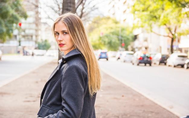 Fashion model standing in half-turn on street