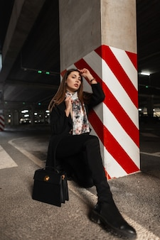Fashion model stylish young woman in fashionable wear with vintage scarf in boots with trendy black leather handbag is sist in the parking lot near the striped pillar. attractive elegant girl posing.
