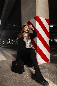 トレンディな黒革のハンドバッグとブーツのヴィンテージスカーフとファッショナブルな服を着たファッションモデルのスタイリッシュな若い女性は、縞模様の柱の近くの駐車場にシストです。魅力的なエレガントな女の子のポーズ。