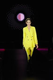 패션 모델은 노란색 pantsuit에 활주로 걸어