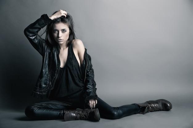 Fashion model wearing leather pants and jacket posing on grey background