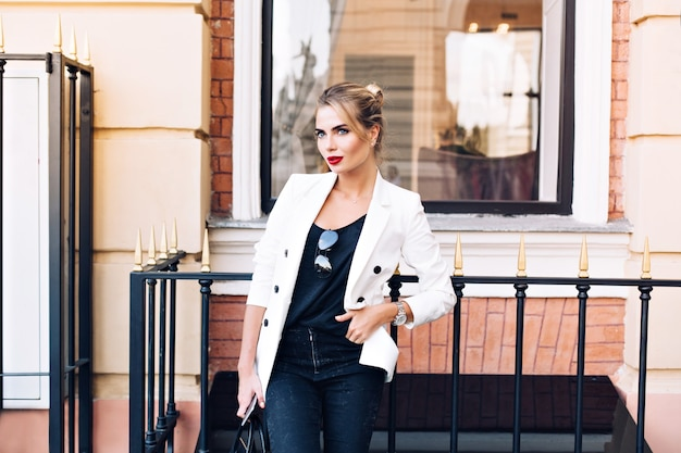 Fashion model in white jacket is leaning on fence on street. she keeps hand in pocket, looking to side.