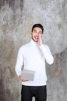 Modello di moda in maglione bianco che tiene una confezione regalo d'argento e chiama o invita qualcuno accanto a lui.