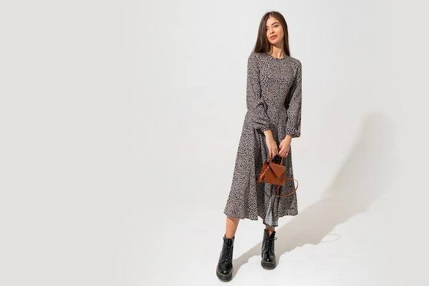 Манекенщица с красивым лицом и идеальным телом. в модном платье, с сумочкой из коричневой кожи. полная длина.