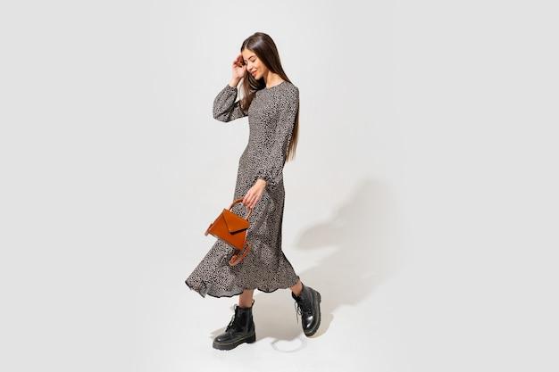 美しい顔と完璧なボディを持つファッションモデル。トレンディなドレスを着て、茶色の革のハンドバッグを持っています。全長。