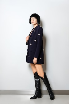 Fashion model with black bob haircut posing near the wall in blue jacket with gems decor and in wide high boots