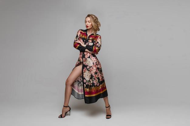 Фотомодель со светлыми волосами и красными губами в стильном платье с рисунком и на черных каблуках. модель стоит с вытянутой вперед правой ногой.