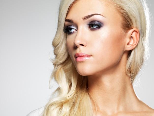 明るいメイクのファッションモデル。長いブロンドの髪を持つ若いファッション女性の肖像画