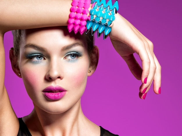 Фотомодель с ярким макияжем и творческой прической женщина с модным макияжем портрет крупным планом