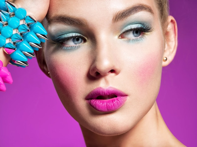 Fashion model with bright makeup and creative hairstyle woman with  fashion makeup closeup portrait