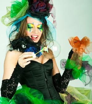 Фотомодель с творческим макияжем, дует мыльные пузыри. кукольный стиль.