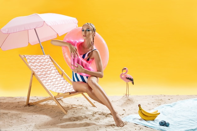 Fashion model with pink swimming circle poses on yellow background