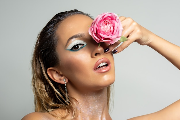 明るい表面にバラの花が咲くファッションモデル。