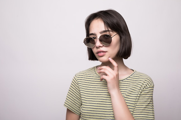 Fashion model with short hair. young girl in sunglasses with hands near face posing