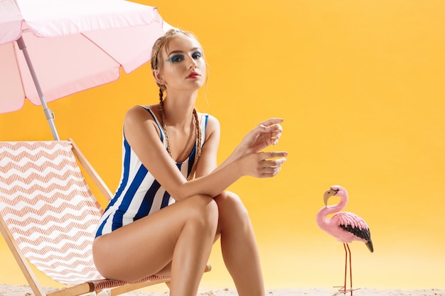 Fashion model with smoky eyes poses on summer decor