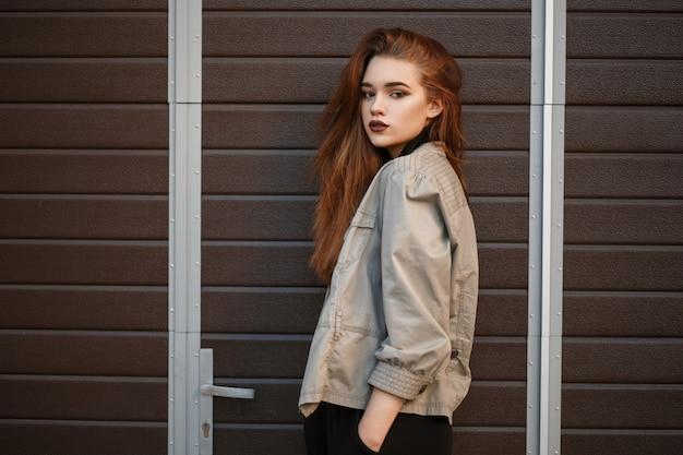 검은 폴로 셔츠와 거리의 문 근처에서 포즈를 취하는 유행 재킷 패션 모델 여자