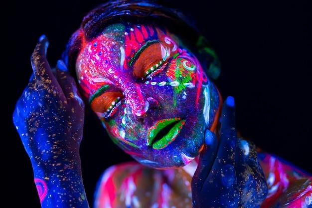 蛍光メイクでネオンの光のファッションモデルの女性。