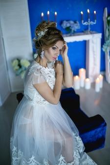 青い部屋で白いロングドレスのファッションモデルの女性