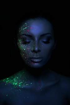 Fashion model woman in neon light bright fluorescent makeup, drop on face