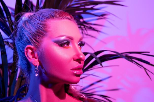 Женщина фотомодели с ярким макияжем в красочных ярких неоновых ультрафиолетовых огнях позирует в студии.