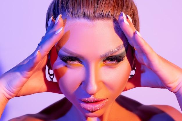 다채로운 밝은 빛에 밝은 화장과 패션 모델 여자는 스튜디오에서 포즈