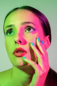 Fashion model woman with a bright makeup in colourful bright neon uv lights posing in studio