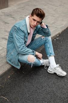 トレンディな白いスニーカーで破れたファッショナブルなブルージーンズのスタイリッシュなデニムジャケットのファッションモデルの若い男は、街の道路の近くの歩道に座っています。屋外の通りでヴィンテージカジュアルな服を着たハンサムな男。
