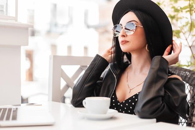 선글라스에 검은색 우아한 아름다운 옷을 입은 패션 모델 젊은 여성이 화창한 날 여름 야외 카페의 빈티지 의자에 앉아 쉬고 있습니다. 매력적인 여자는 휴식을 취했습니다. 좋은 주말.