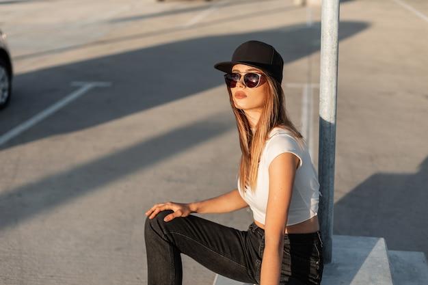ファッショナブルな夏のカジュアルな服を着たクールな黒い帽子の黒いサングラスのファッションモデルの若い女性は、駐車場で休んで晴れた日を楽しんでいます。アメリカのモダンな外観。