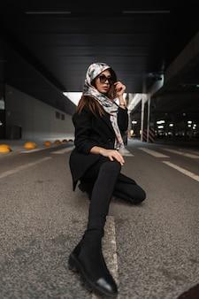 街のアスファルトに座ってポーズをとるブーツの若者のジーンズのトレンディな黒のコートで頭にシルクのエレガントなスカーフでスタイリッシュなサングラスをかけたファッションモデルの若い女性。ビジネスの女の子はアスファルトでリラックスします。