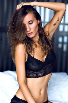Ritratto di mattina di moda di bella donna sexy bruna timida che indossa lingerie di lusso glamour, in posa da solo nella sua camera da letto, stile boudoir