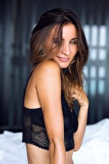 彼女の寝室で一人でポーズをとる、豪華な魅力的なランジェリーを身に着けている美しい恥ずかしがり屋のブルネットのセクシーな女性のファッションの朝の肖像画、私室スタイル