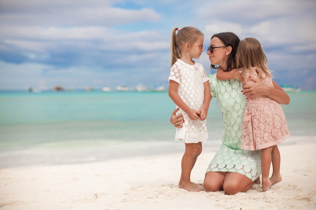 Fashion mother and two her adorable daughters at exotic beach on sunny day