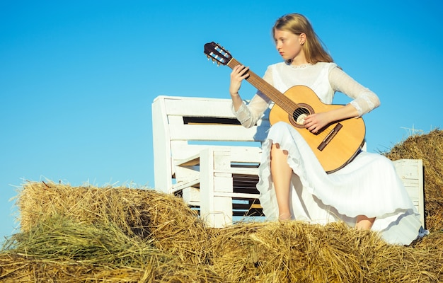 日当たりの良い自然に白いドレスを着たファッションミュージシャン。