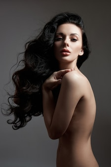 Fashion nude woman posing with long hair