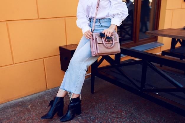 ファッションオブジェクト。バッグとサングラスをかけた女性の手。屋外に座っているファッショナブルな女の子。スタイリッシュなジーンズ。