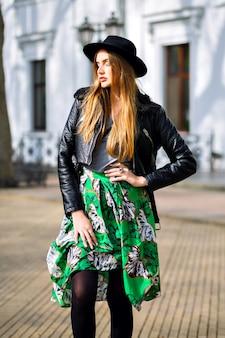 Модный открытый городской портрет стильной хипстерской женщины, идущей по улице и веселой, молодой женщины-путешественника, модницы, женской красоты, длинной винтажной юбки, ретро шляпы и байкерской куртки.