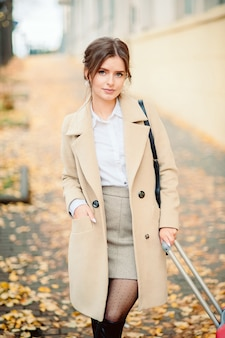 Fashion outdoor photo of beautiful ladylike woman with dark straight hair wearing elegant coat and felt hat, posing in autumn park