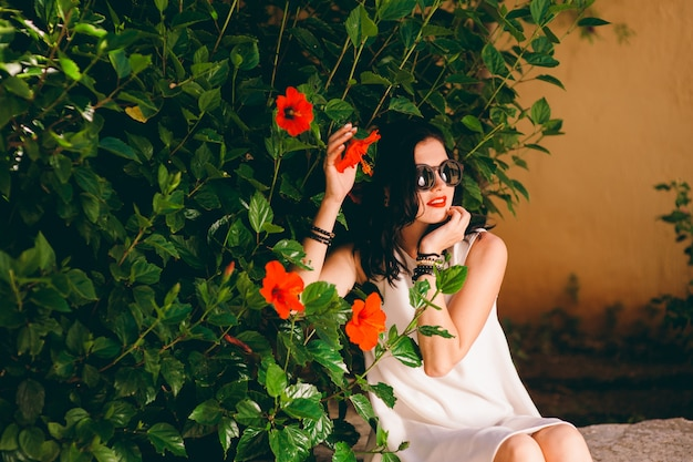 Fashion outdoor photo of beautiful sensual woman with dark hair in luxurious white dress