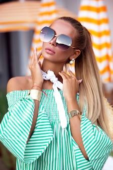 エレガントなドレスと豪華なヨットでリラックスしたアクセサリーのブロンドの髪と美しい官能的な女性のファッション屋外写真。